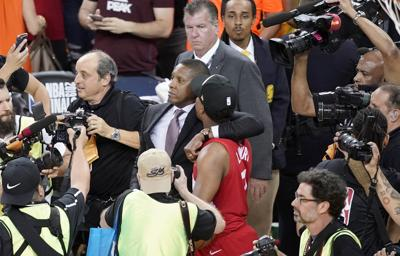 Toronto Raptors general manager Masai Ujiri, center left, walks with guard Kyle Lowry after the Raptors defeated the Golden State Warriors in Game 6 of the NBA Finals in Oakland, California. Authorities said they are investigating whether Ujiri pushed and hit a sheriff's deputy in the face as he tried to get on the court after his team won the NBA title. — AP Photo/Tony Avelar