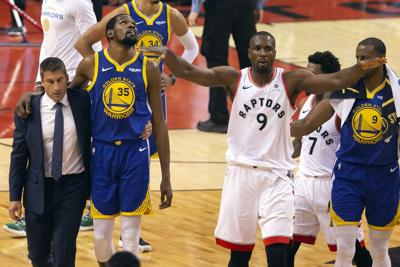 Golden State Warriors forward Kevin Durant (35) walks off the court after sustaining an injury as Toronto Raptors center Serge Ibaka (9) gestures to the crowd during first half basketball action in Game 5 of the NBA Finals in Toronto on Monday. — Chris Young/The Canadian Press via AP