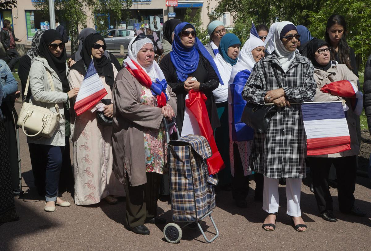 In this May 16, 2014 file photo, women wear muslim scarf and hold French flags gather outside the town hall of Mantes la Ville, northwest of Paris. The French Senate approved a bill on Tuesday proposed by the mainstream right that would oblige women wearing headscarves to remove them when accompanying school outings. The bill has almost no chance of becoming law since the lower chamber, controlled by President Emmanuel Macron's centrist party, will almost certainly axe it. — AP Photo/Michel Euler, File)