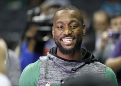 Boston Celtics' Kemba Walker smiles with friends as he makes his way onto the Charlotte Hornets' court before an NBA basketball game between the Celtics and the Hornets in Charlotte, North Carolina on  Thursday. Walker formerly played for the Hornets. — AP Photo/Bob Leverone