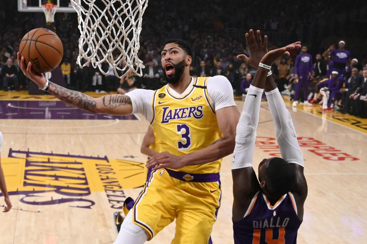 Los Angeles Lakers forward Anthony Davis, left, shoots as Phoenix Suns forward Cheick Diallo defends during a game Monday in Los Angeles. — AP Photo/Mark J. Terrill