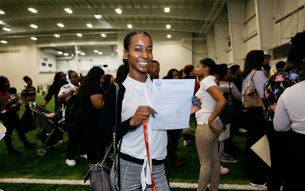 A student holds an acceptance letter
