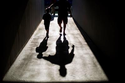 In this April 26, 2014 file photo, a father and son cast a shadow as they walk through a tunnel before the start of a baseball game in Atlanta. A rigorous U.S. government-led study released on Tuesday found that zinc and folic acid supplements don't boost men's fertility, despite promotional claims that they do.— AP Photo/David Goldman