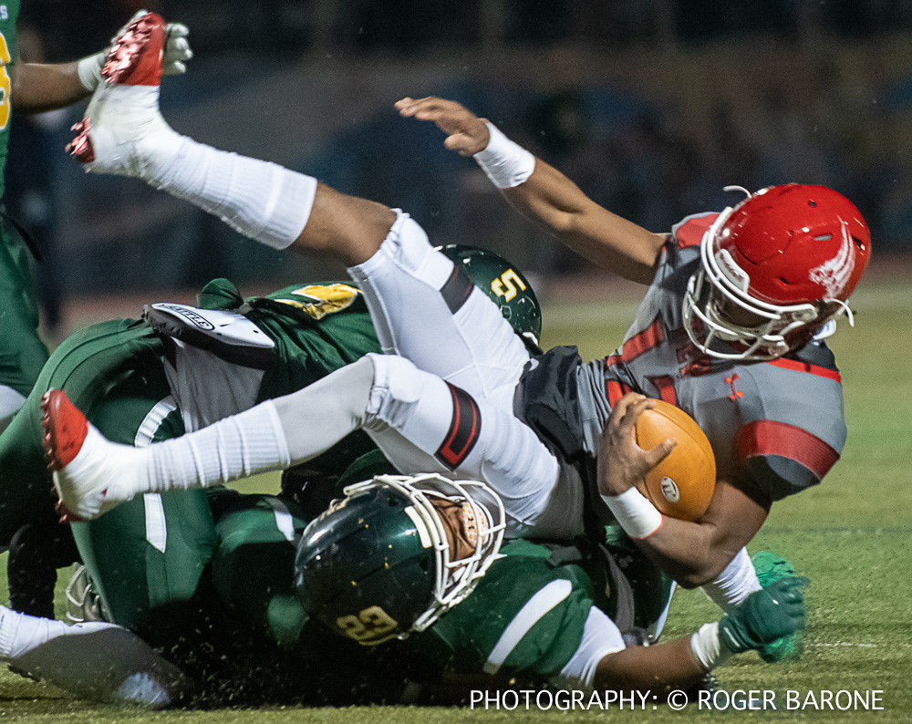 Imhotep quarterback Jalen Sutton-Christian is taken down after a short gain. — PHOTO: © ROGER BARONE