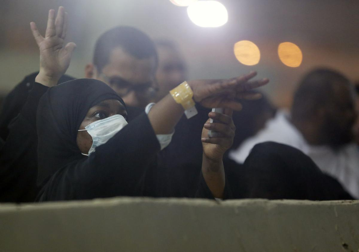 """Muslim pilgrims cast stones at a pillar symbolizing the stoning of Satan, in a ritual called """"Jamarat,"""" the last rite of the annual hajj, on the first day of Eid al-Adha, in Mina near the holy city of Mecca, Saudi Arabia, on Sunday. The hajj is required of all Muslims to perform once in their lifetime if they are financially and physically able. — AP Photo/Amr Nabil"""