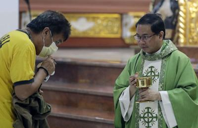 Catholic priest Fr. Joseph Arellano, right, looks at a man who forgot to take off his protective mask and tried to insert the host in his mouth during communion at a mass at the Minor Basilica of San Lorenzo Ruiz in Manila's Chinatown, Philippines. — AP Photo/Aaron Favila