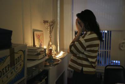 "In this Jan. 3 photo, Chana Blum, 14, recites a blessing after lighting candles for Shabbat dinner in her family's home in New York. Two days later, Blum joined her older sister at the ""No Hate, No Fear"" solidarity march organized by New York's Jewish community in response to the recent string in anti-Semitic attacks. —AP Photo/Jessie Wardarski"