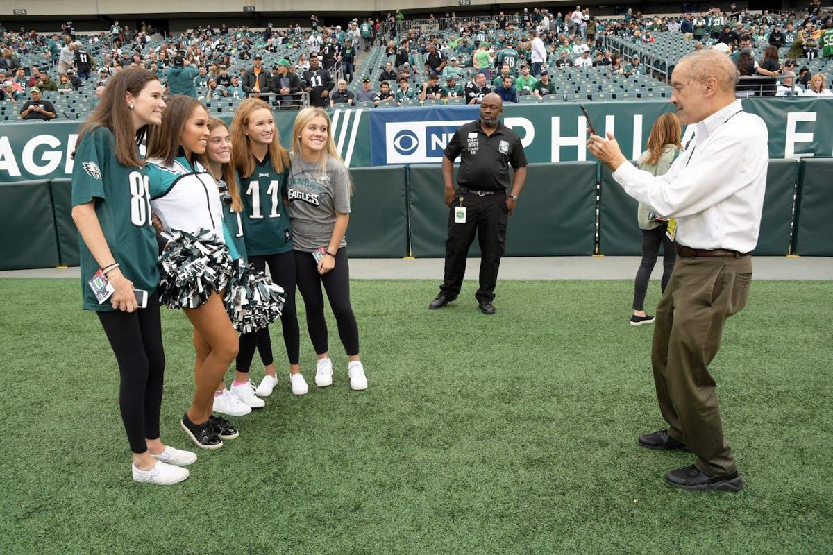 Philadelphia Tribune sportswriter Donald Hunt, right, takes a picture of Eagles fans who stand with his daughter and Philadelphia Eagles cheerleader Arielle Hunt, second from left, prior to the kickoff of an Eagles game at Lincoln Financial Field.