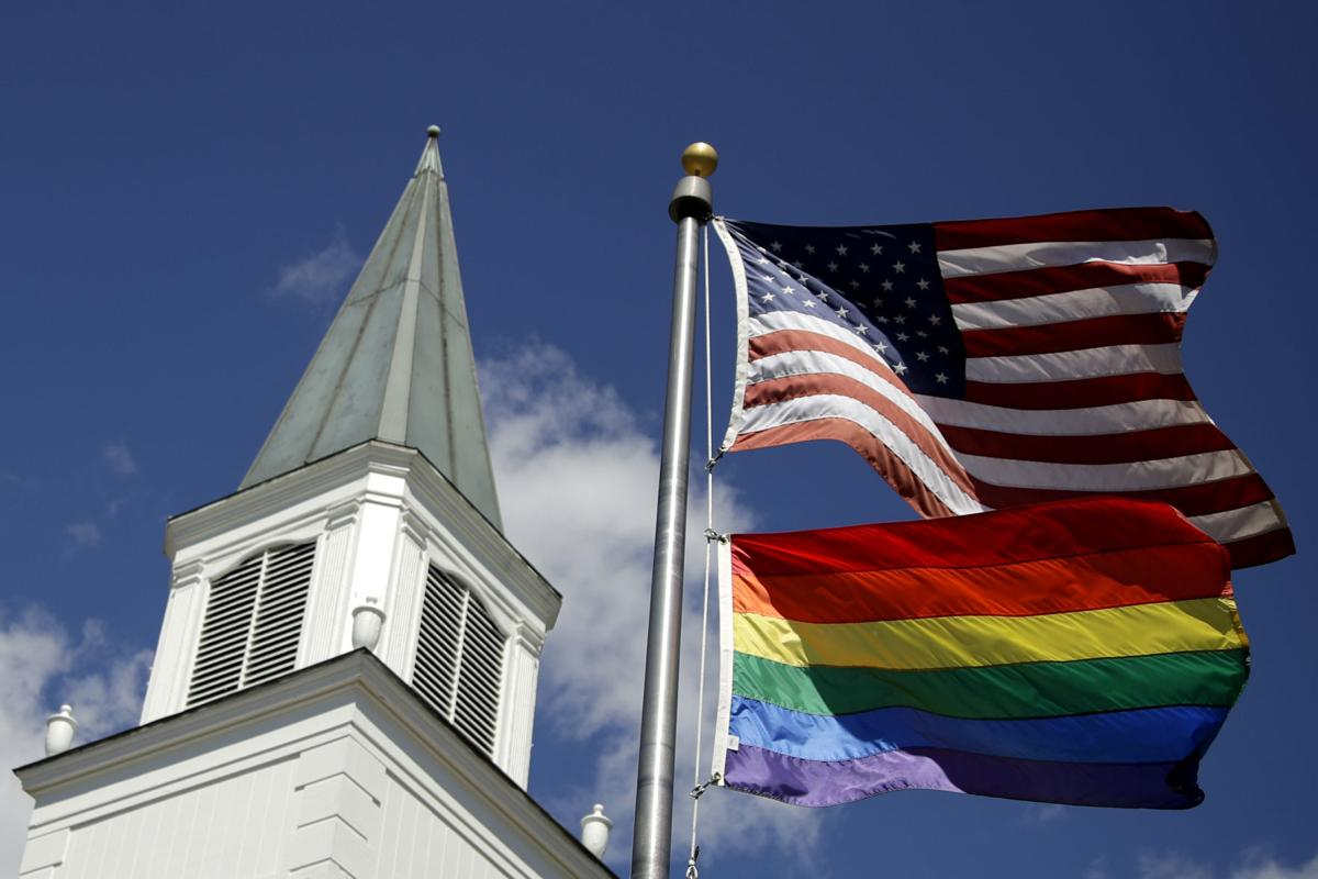 A gay pride rainbow flag flies along with the U.S. flag in front of the Asbury United Methodist Church in Prairie Village, Kan. A new Associated Press-NORC Center for Public Affairs Research poll shows age, education level and religious affiliation matter greatly when it comes to Americans' opinions on a prospective clergy member's sexual orientation, gender, marital status or views on issues such as same-sex marriage or abortion — AP Photo/Charlie Riedel