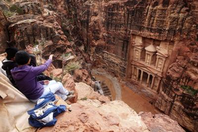 """In this Feb. 13, 2017 file photo, tourists point at the Treasury, in the kingdom's Petra archaeological park, southern Jordan. A fictional caper about an antiquities heist set Petra has stirred widespread outrage over the film's portrayal of historical Jewish ties to Jordan, shining a light on the tenuous peace with neighboring Israel and prompting the government to suspend the movie's production. """"Jaber"""" follows a Jordanian boy who uncovers a stone with a Hebrew inscription on it in the rose-colored, rock-hewn city of Petra. — AP Photo/Sam McNeil, File"""