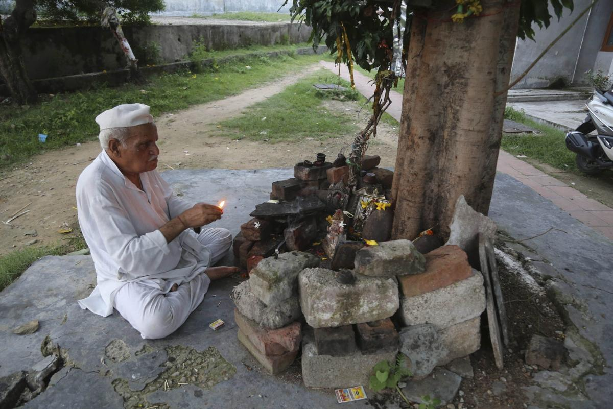 Kashmiri Hindu man, Sham Lal, 63 performs evening prayers at the Muthi migrant camp in Jammu, India. Tens of thousands of Kashmiri Hindus fled the restive region nearly 30 years ago, and the ghost of insurgency and their mass exodus still haunts them. They celebrated after India's Hindu nationalist-led government stripped political autonomy from its part of Muslim-majority Kashmir on Aug. 5. Kashmiri Hindus view it as a step toward justice and possible return to their homeland. But many are still wary of returning. —AP Photo/Channi Anand