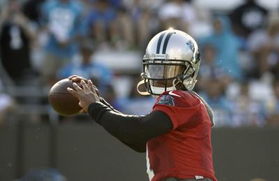 Carolina Panthers quarterback Cam Newton looks to pass during practice at the NFL football team's training camp in Spartanburg, N.C. — AP Photo/Chuck Burton