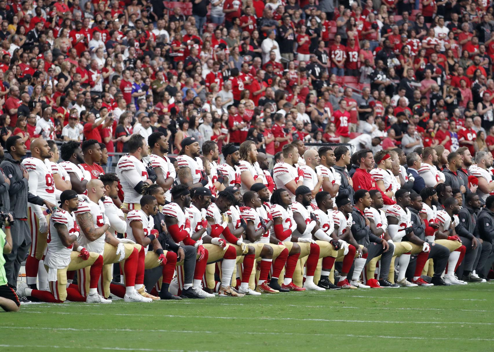 San Francisco 49ers players kneel during national anthem