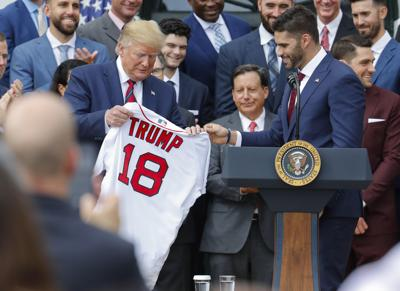 Boston Red Sox outfielder J.D. Martinez, right, presents a team jersey to President Donald Trump, left, during a ceremony on the South Lawn of the White House in Washington on Thursday.  Trump honored the 2018 World Series baseball champion Red Sox. — AP Photo/Pablo Martinez Monsivais