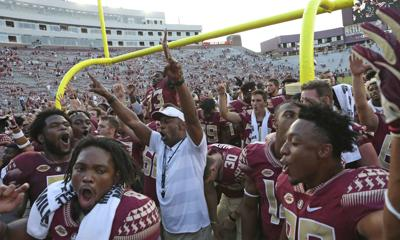 In this Sept. 22, 2018 file photo Florida State head coach Willie Taggart, center, celebrates a win with his team at the end of an NCAA college football game against Northern Illinois in Tallahassee Fla. Decades of Florida State football dominance is displayed on the walls just outside of Taggart's office. Trophies and plaques commemorate All-America players and championship teams. Lots of them. Taggart takes responsibility for last year's 5-7 finish, but remains confident in his plan to get Florida State back on track because it has worked before. — AP Photo/Steve Cannon, file