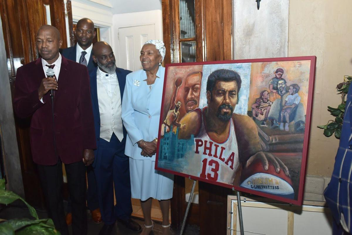 Jay Bagley, Marc Jackson, Terrell Johnson and Selina Gross marvel at a painting of late basketball superstar Wilt Chamberlain. Johnson was the artist who depicted Chamberlain on and off the court. — TRIBUNE PHOTOS BY RONALD GRAY