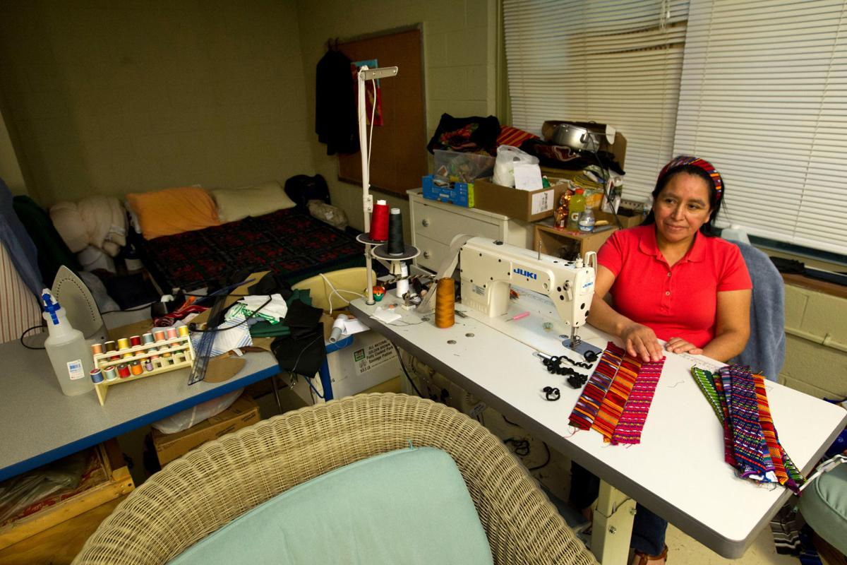 Maria Chavalan-Sut, an immigrant from Guatemala, shows her handmade headbands, sitting at her sewing machine, in her room at the Wesley Memorial United Methodist Church in Charlottesville, Va. She uses fabric that a son has mailed to her from Guatemala to make a range of goods. She can't sell them, but she accepts donations in exchange. — AP Photo/Jose Luis Magana