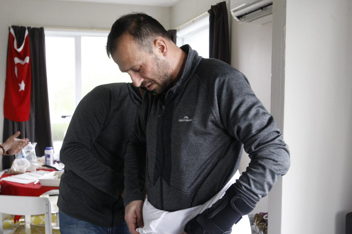 Temel Atacocugu, who was shot nine times during the Christchurch mosque attacks, tries on the clothes he will wear during the Hajj pilgrimage, in Christchurch, New Zealand.— AP Photo/Nick Perry