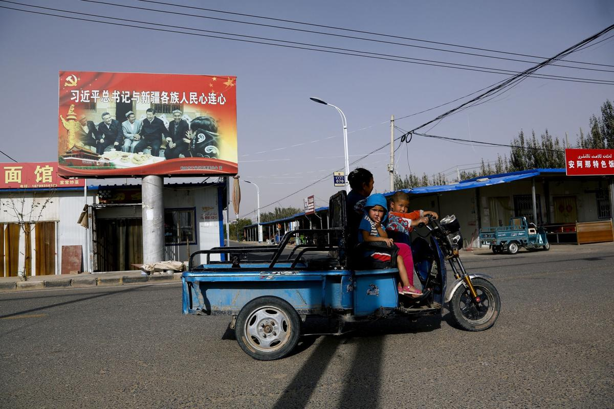 In this Sept. 20, 2018, file photo, an Uighur woman shuttles school children on an electric scooter as they ride past a propaganda poster showing China's President Xi Jinping joining hands with a group of Uighur elders in Hotan, in western China's Xinjiang region. — AP Photo/Andy Wong, File