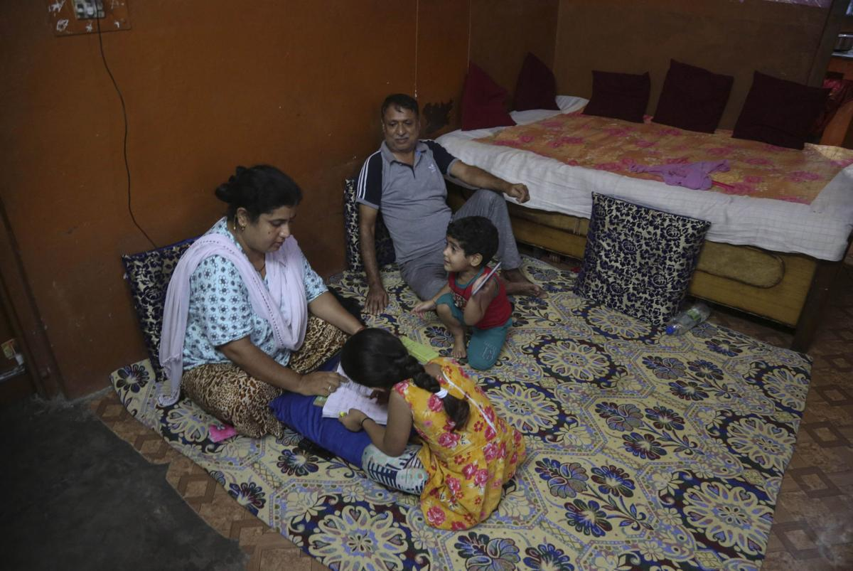 A Kashmiri Hindu family spends an evening inside their residence at Muthi migrant camp in Jammu, India. — AP Photo/Channi Anand