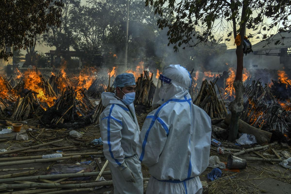 Relatives stand in front of funeral pyres