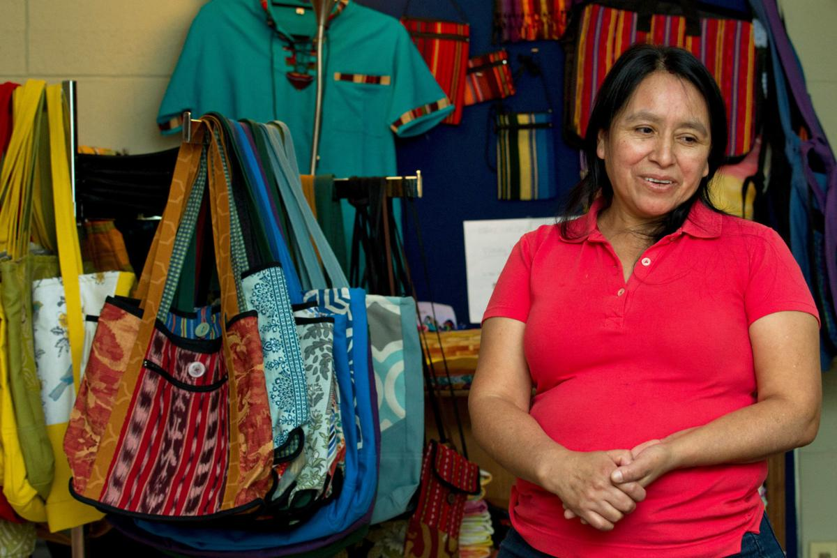 Maria Chavalan-Sut of Guatemala stands next to items she has made at the Wesley Memorial United Methodist Church in Charlottesville, Va.— AP Photo/Jose Luis Magana