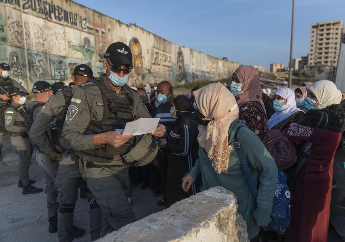 Palestinian women wait to cross