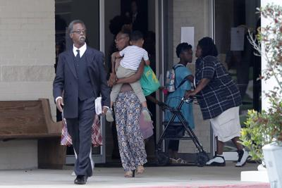 Congregants exit after services at the Life Tabernacle Church in Central, La. on Sunday. Pastor Tony Spell has defied a shelter-in-place order by Louisiana Gov. John Bel Edwards, due to the new coronavirus pandemic, and continues to hold church services with hundreds of congregants. — AP Photo/Gerald Herbert