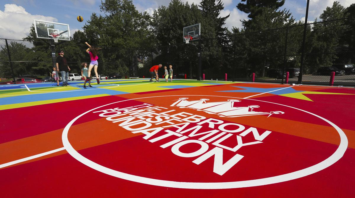 Students shoot around after the debut of the new basketball court at I Promise School, on Wednesday in Akron, Ohio. James helped unveil the multicolored outdoor court at the school, which has just started its second academic year and now serves more than 300 students from grades 3-5. — Jeff Lange/Akron Beacon Journal via AP