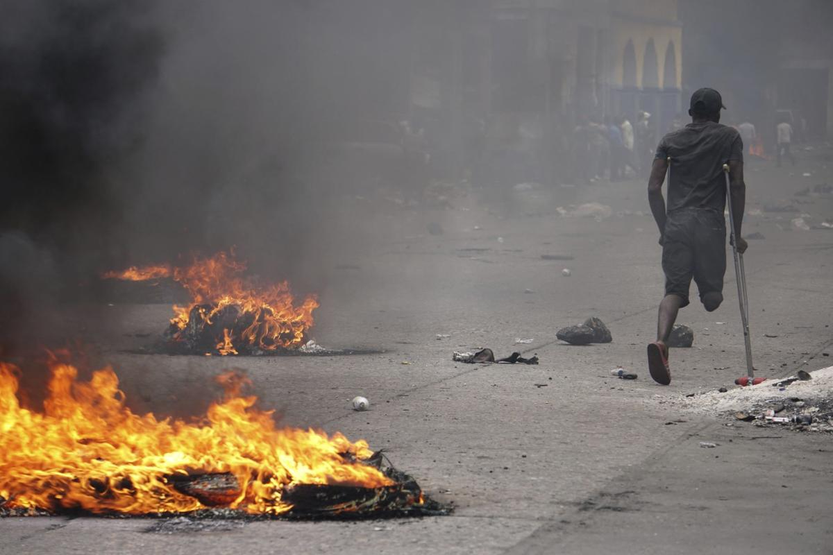 DEMONSTRATING  A protester on crutches passes burning tires during a demonstration to demand the resignation of President Jovenel Moise in Port-au-Prince, Hait. Opposition leaders in Haiti launched a two-day strike that paralyzed the country's capital amid another day of protests demanding that President Jovenel Moise resign over corruption allegations.—AP Photo/Edris Fortune