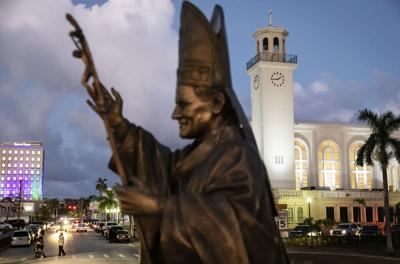 A statue of Pope John Paul II stands outside the island's main cathedral, Dulce Nombre de Maria Cathedral-Basilica, during a Mass in Hagatna, Guam. Those old enough to remember often cite the pontiff's visit to the island in 1981 as the most thrilling event of their lifetimes, memorialized by the bronze statue of the now-sainted pope designed to slowly rotate on a concrete pedestal. — AP Photo/David Goldman