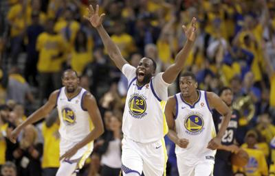 Golden State Warriors' Draymond Green, center, reacts after feeding an alley-oop pass for a dunk by Kevin Durant during the first half in Game 1 against the New Orleans Pelicans in Oakland, Calif. — AP Photo/Marcio Jose Sanchez, File