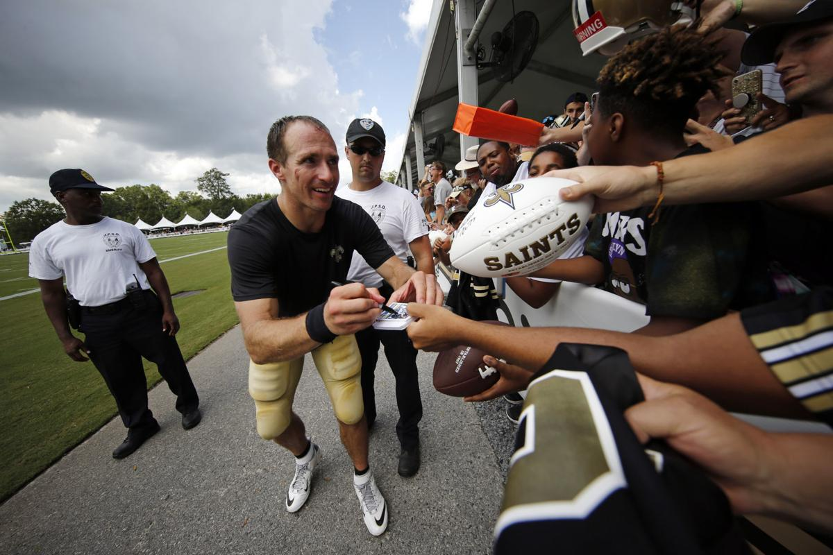 New Orleans Saints quarterback Drew Brees signs autographs for fans after training camp at their NFL football training facility in Metairie, La. — AP Photo/Gerald Herbert