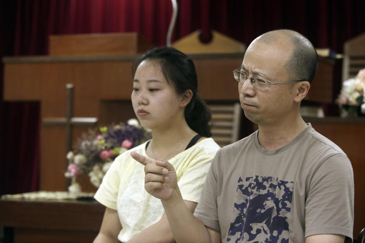 Liao Qiang, right, and his daughter Ren Ruiting speak during an interview with The Associated Press at a church in Taipei, Taiwan. Liao arrived in Taiwan last week after fleeing China with five family members. They plan to seek asylum in the United States. — AP Photo/Chiang Ying-ying