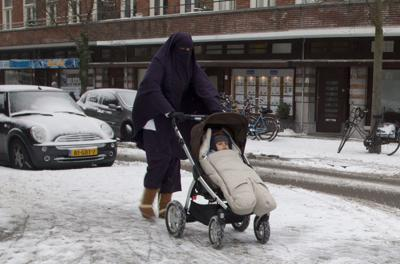 In this Monday Jan. 21, 2013 file photo, a woman wearing a full-face veil known as niqab, pushes a baby stroller on snow-covered streets in Amsterdam, Netherlands. A new Dutch law came into force Thursday banning face-covering clothing — including the burqa and niqab worn by conservative Muslim women — on public transport, in government buildings and at health and education institutions. —  AP Photo/Peter Dejong, File