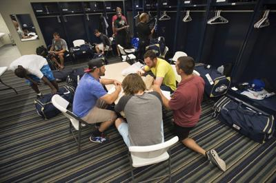 """Members of the Biloxi Shuckers minor league baseball team eat lunch before practice at the Pensacola Blue Wahoos' stadium in Pensacola, Florida. Minor leaguers at the lowest levels can make as little as $1,100 per month despite spending 50-to-70 hours per week at the ballpark. A lawsuit alleging MLB violated minimum wage and overtime requirements was pre-empted in 2018 when Congress passed the """"Save America's Pastime Act,"""" which stripped minor leaguers of the protection of federal minimum wage laws. —AP Photo/Michael Spooneybarger, File"""