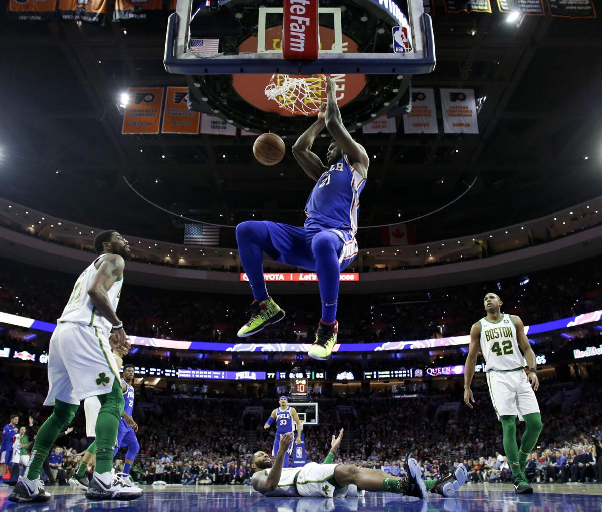 Philadelphia 76ers' Joel Embiid (21) dunks as Boston Celtics' Kyrie Irving, Marcus Morris and Al Horford, from left, watch