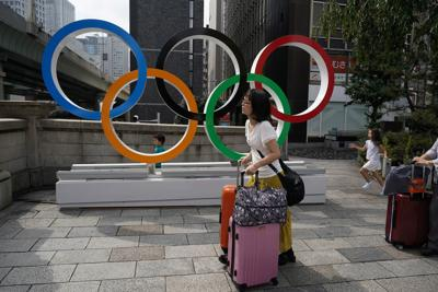 In this Aug. 19 file photo, tourists walk with their luggage past the Olympic rings in Tokyo. Frustrated residents of Japan got another shot at attending next year's Tokyo Olympics when organizers on Friday put about 1 million more tickets into the latest lottery. — AP Photo/Jae C. Hong, File