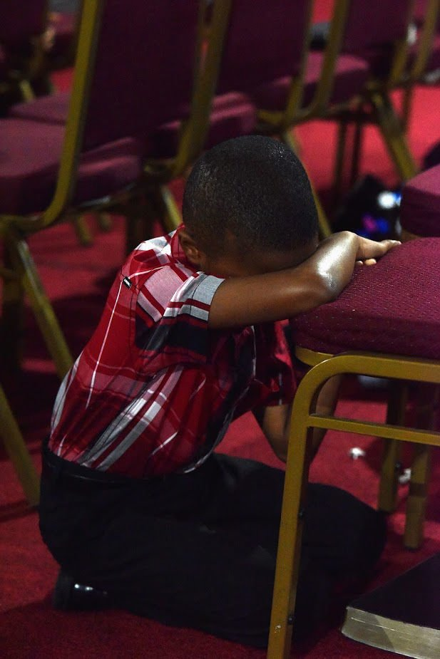 A child takes and moment to pray.