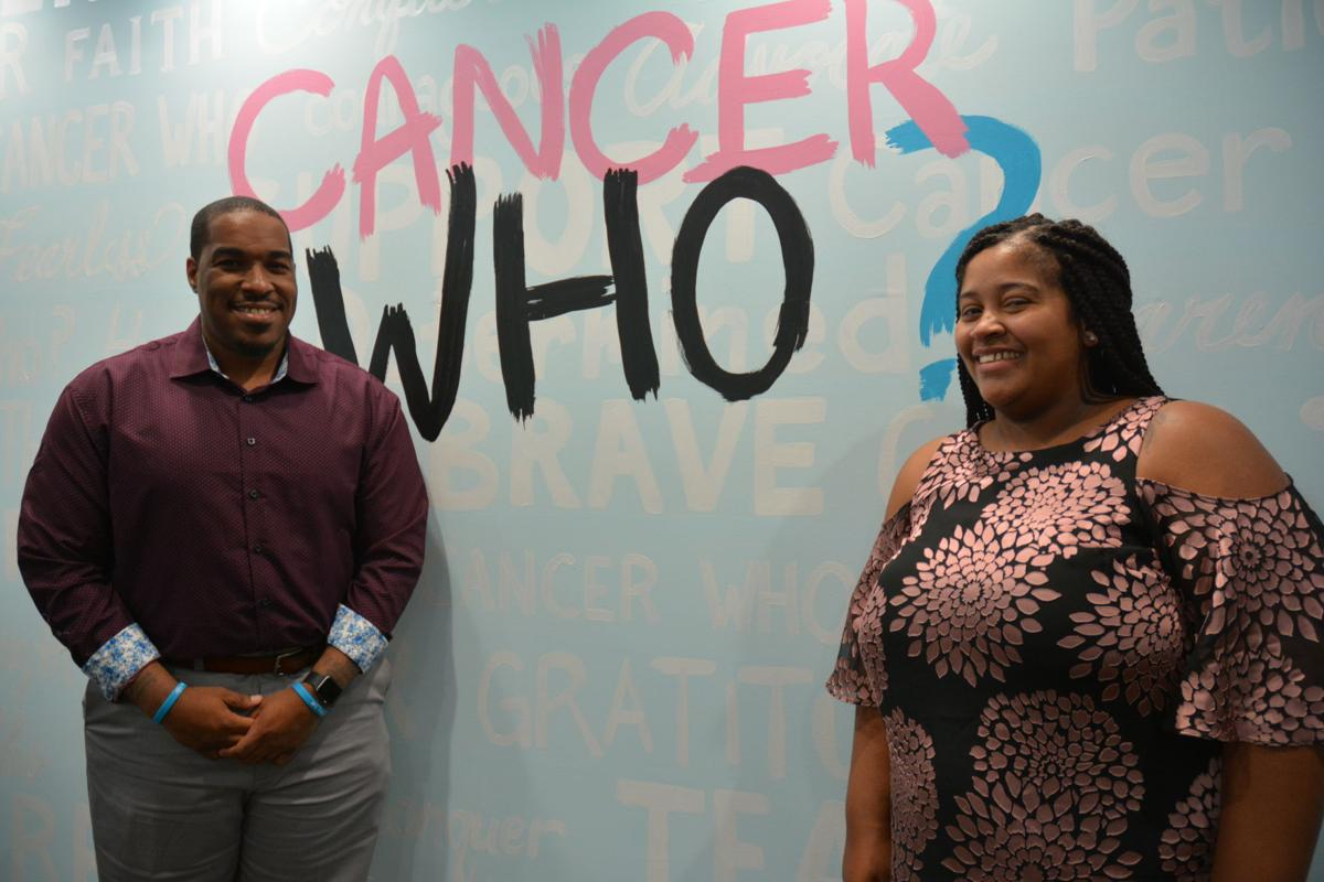 Cancer WHO? Founders Al and Marjani Harris in front of a wall of encouragement. The wall lists positive words such as faith, brave and gratitude.