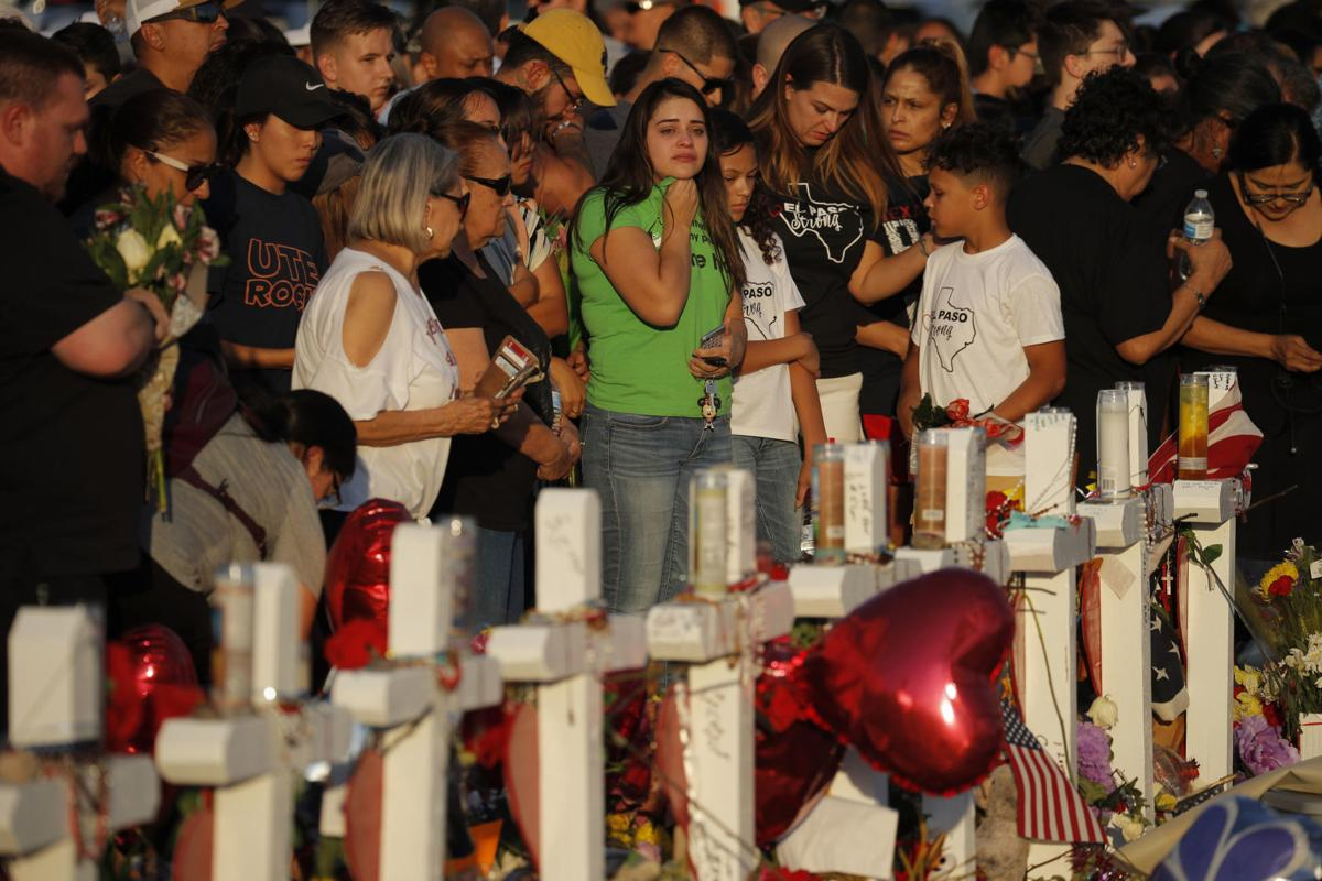 In this Aug. 6 file photo, people visit a makeshift memorial at the scene of a mass shooting at a shopping complex in El Paso, Texas. At the growing memorial for the victims of the massacre, the city's roots in Catholicism and religion in general loom large. — AP Photo/John Locher, File