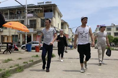 In this June 5, 2019, photo, residents of the Hui Muslim ethnic minority walk in a neighborhood near an OFILM factory in Nanchang in eastern China's Jiangxi province. The Associated Press has found that OFILM, a supplier of major multinational companies, employs Uighurs, an ethnic Turkic minority, under highly restrictive conditions, including not letting them leave the factory compound without a chaperone, worship, or wear headscarves. — AP Photo/Ng Han Guan