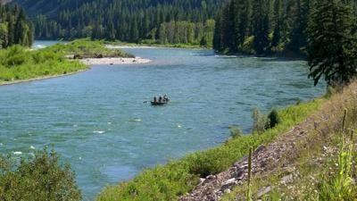 wide shot of fishing dift boat navigating the snake river