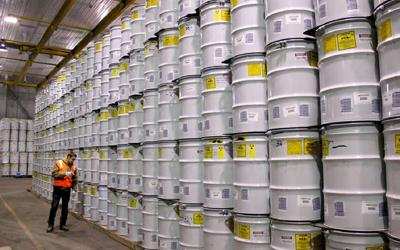 An employee at the Advanced Mixed Waste Treatment Plant west of Idaho Falls inspects barrels of treated transuranic waste that are waiting to be shipped to the U.S. Department of Energy's Waste Isolation Pilot Plant near Carlsbad, N.M.  Courtesy photo - Fluor Idaho
