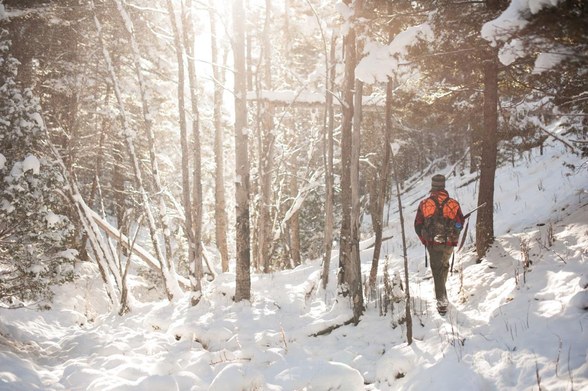 Male Hunter Walking through snowy forest backlit by sunshine