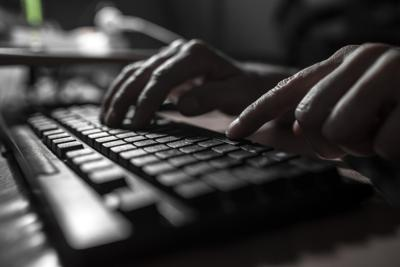 Fingers pressing on a computer keyboard in the dark .
