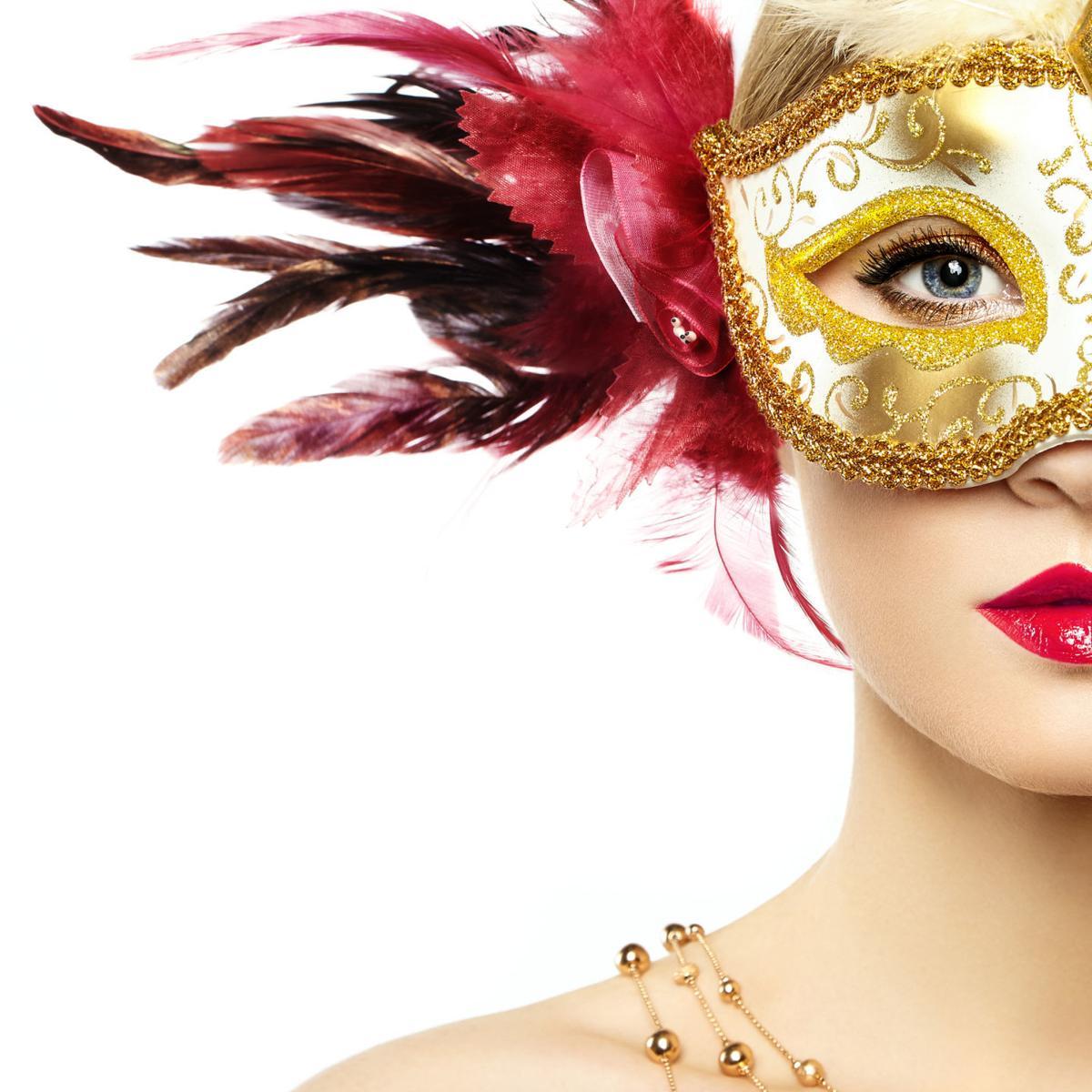Beautiful young woman in mysterious golden Venetian mask