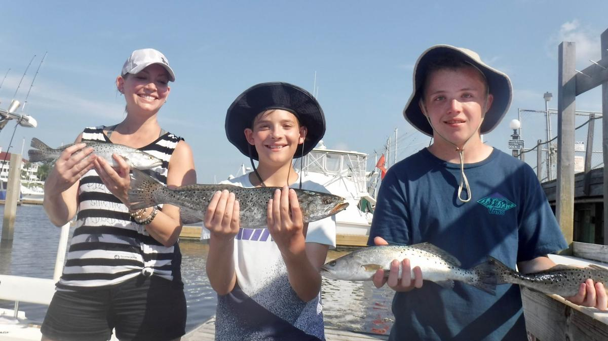 Happy anglers display some of their sea trout
