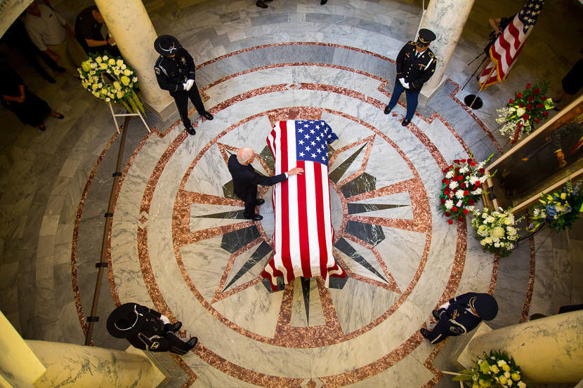 Former Gov. Phil Batt touches the casket of fellow former Gov. Cecil Andrus in the Statehouse rotunda Wednesday.