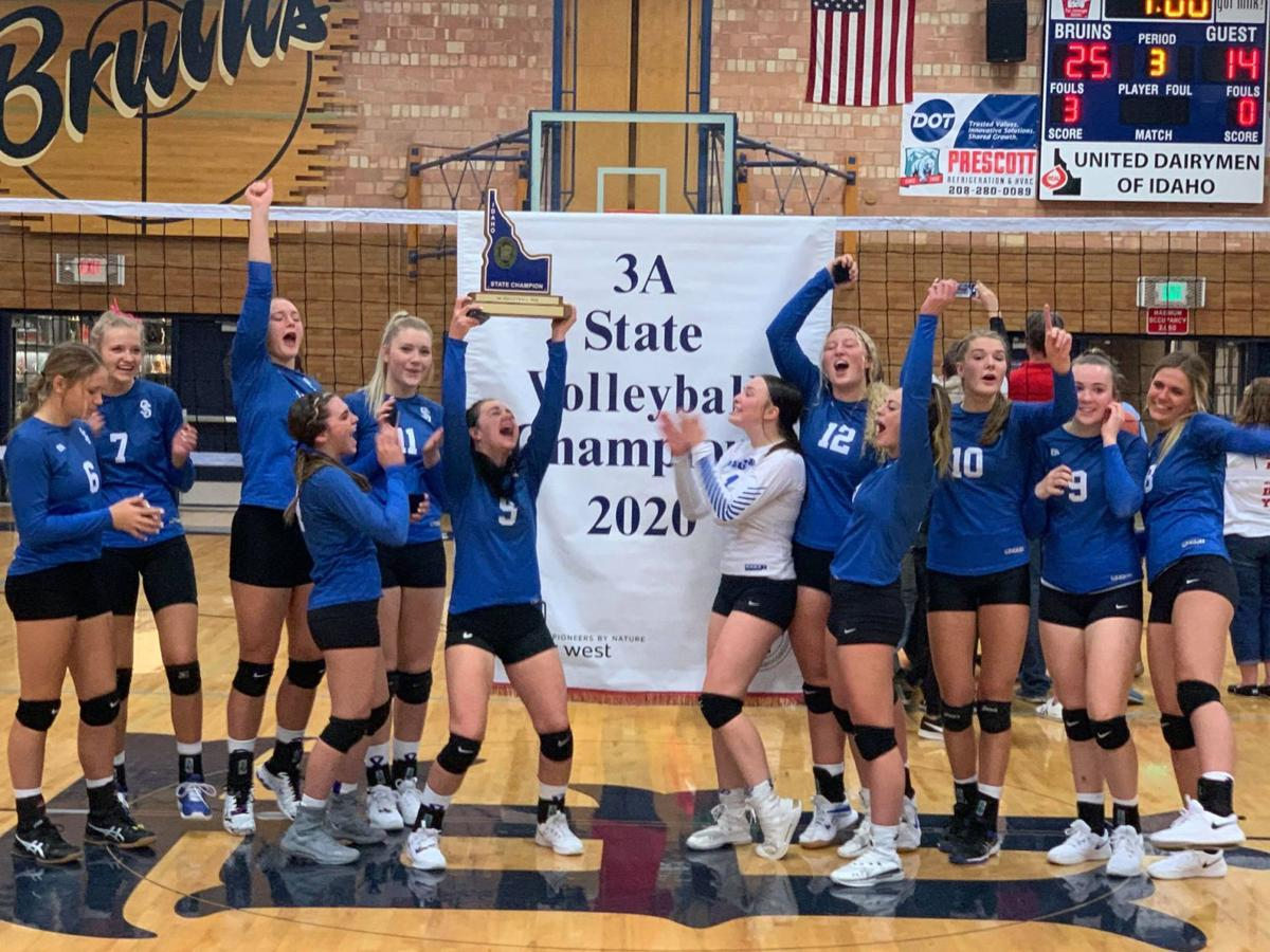 Sugar-Salem's volleyball team celebrates with their trophy and banner after sweeping the state tournament to win their second straight state title.